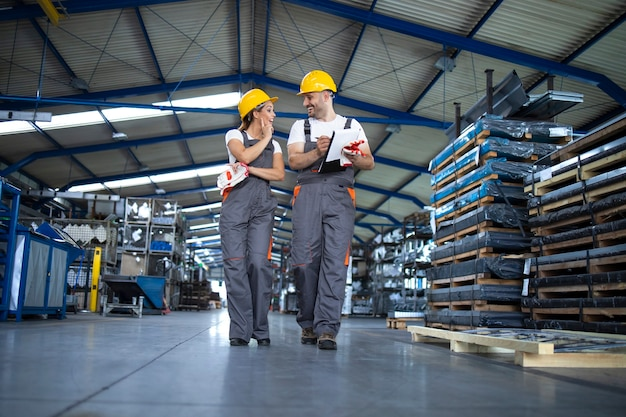 Factory workers in work wear and yellow helmets walking through industrial production hall and discussing about improving efficiency Free Photo