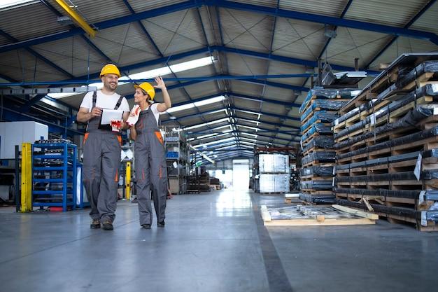 Operai in abiti da lavoro e caschi gialli che camminano attraverso il capannone di produzione industriale e discutono dell'organizzazione Foto Gratuite