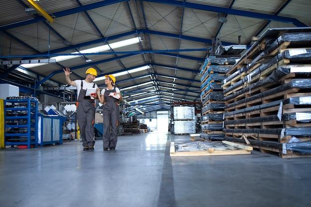 Operai in abiti da lavoro e caschi gialli che camminano attraverso i capannoni di produzione industriale e condividono idee sull'organizzazione Foto Gratuite