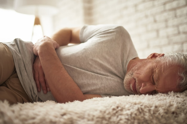 Fainting old man in bed belly pain stomach ache. Premium Photo
