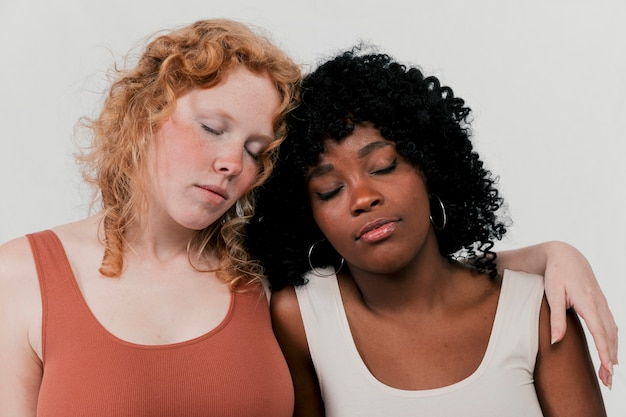 Fair and dark skin women leaning to each other sleeping against grey background Free Photo