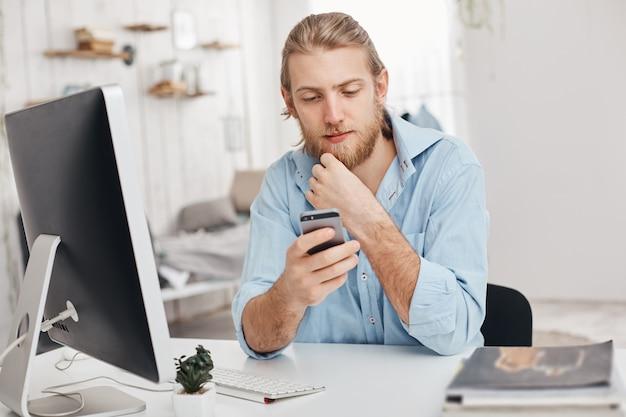 金髪のひげを生やした男性のフリーランサーがスマートフォンに新しいアプリをインストールし、コンピューターにプログラムをダウンロードし、wi-fiを使用し、パートナーからのメッセージを受信します。ビジネス、現代技術、通信 無料写真