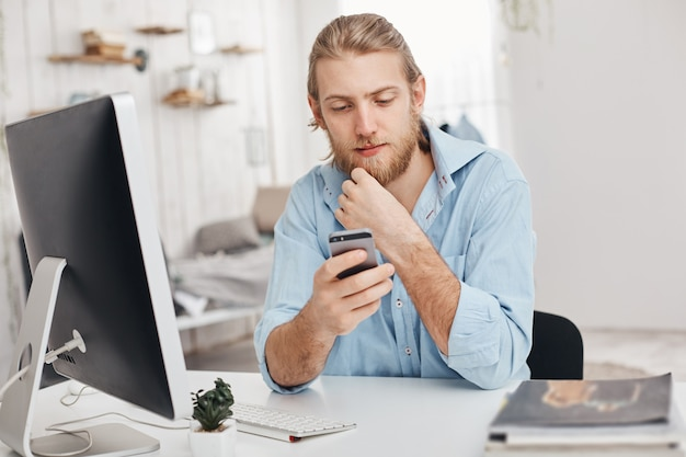 Fair-haired bearded male freelancer installs new app on smart phone, downloads program on computer, uses wi-fi, recieves message from partner. business, modern technologies, communication Free Photo