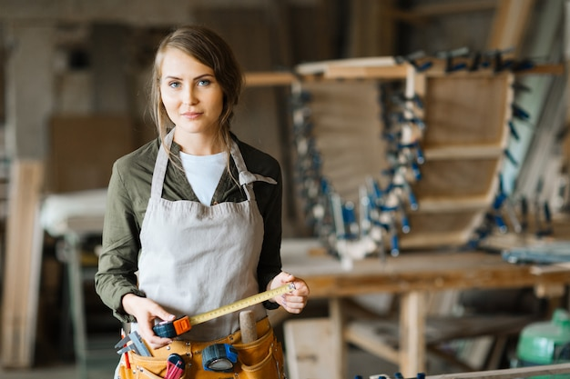 Fair-haired woodworker with tape measure Free Photo