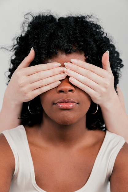 Fair skinned hands of woman closing the eye of an african woman Free Photo