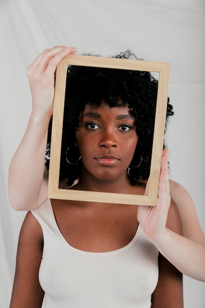 Fair skinned hands of woman holding wooden border frame in front of an african woman Free Photo