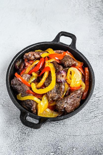 Традиционное мексиканское блюдо из говядины фахитас на сковороде Premium Фотографии