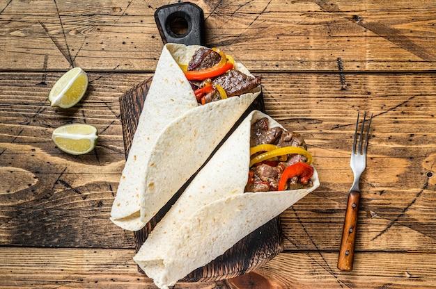 Ролл fajitas tortilla с полосками говядины, цветным болгарским перцем, луком и сальсой Premium Фотографии
