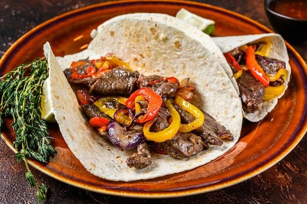 Роллы fajitas tortilla с полосами стейка из говядины, сладким перцем и луком Premium Фотографии