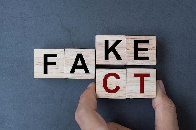 Fake to fact word on table background. Premium Photo