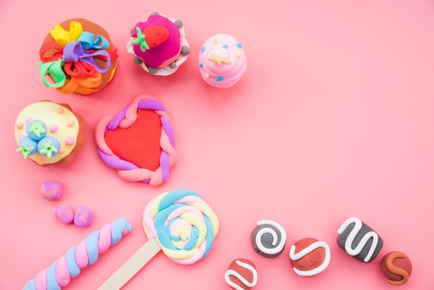Fake handmade cookies and cake made with clay on pink background Free Photo