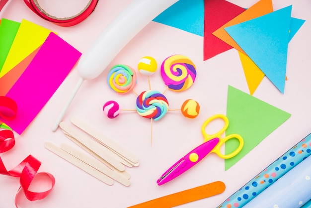 Fake lollipop with crafts equipment with scissors on pink background Free Photo