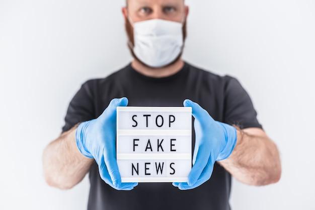 Covid-19パンデミックコンセプト中のフェイクニュースインフォデミック。テキスト付きのライトボックスを持っている手に保護マスクと医療用手袋を着用している男偽のニュースを停止します。人々はコロナウイルスについての真実を知りたがっています Premium写真
