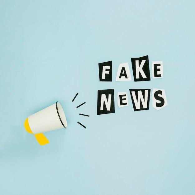 Fake news and megaphone on blue background Premium Photo