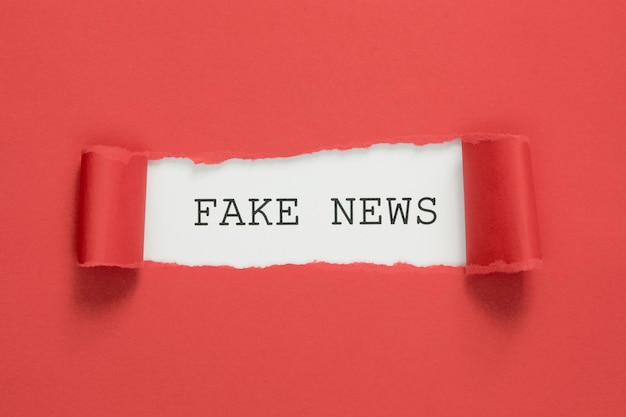Fake news words torn in red paper Free Photo
