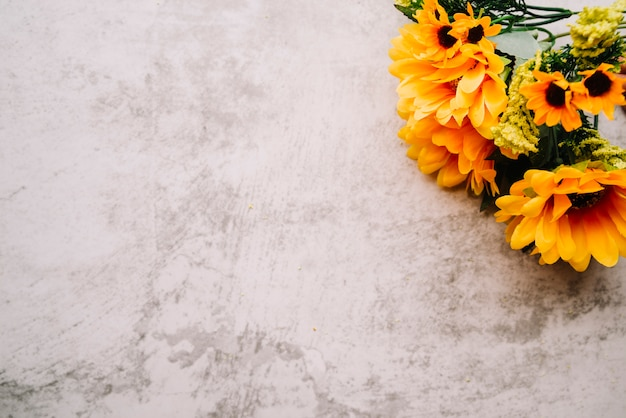 Fake sunflowers bouquet on an old white wall Free Photo