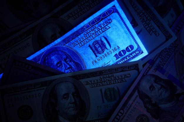 Fake us dollar bill in uv light Premium Photo