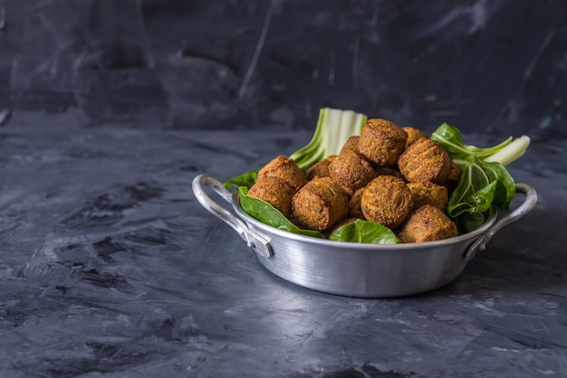 Falafel balls served in plate with green leafs on wooden black background Premium Photo