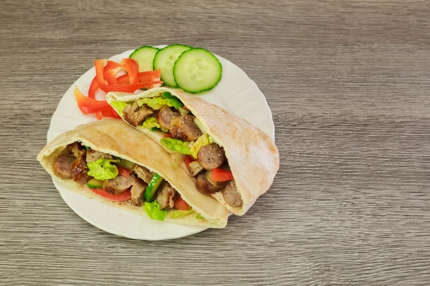 Falafel and fresh vegetables in pita bread on wooden Premium Photo