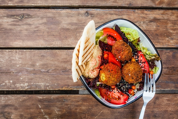 Falafel salad with hummus, beetroot and vegetables in bowl on wooden table, top view. Premium Photo