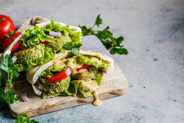 Falafel with fresh vegetables and tahini dressing in pita bread on the board. healthy vegan food concept. Premium Photo