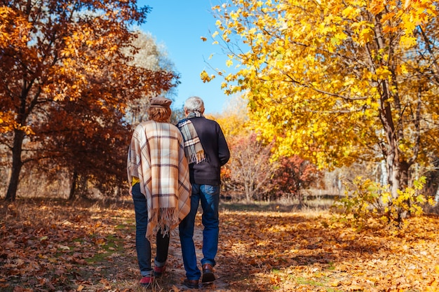 Fall activities. senior couple walking in autumn park. middle-aged man and woman hugging and chilling outdoors Premium Photo
