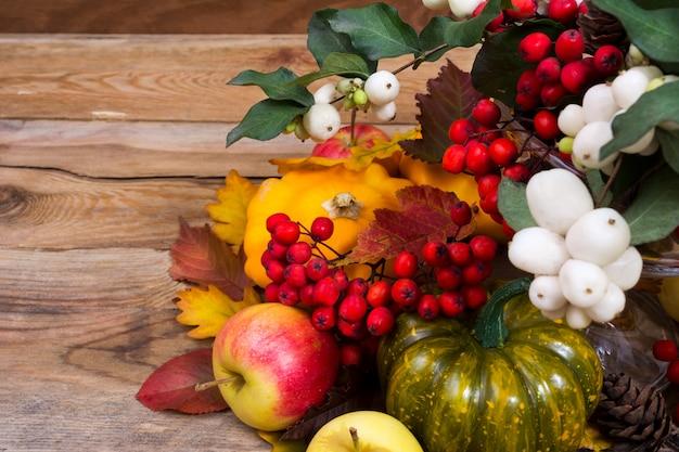 スノーベリー、ナナカマド、緑と黄色のスカッシュと秋の背景 Premium写真