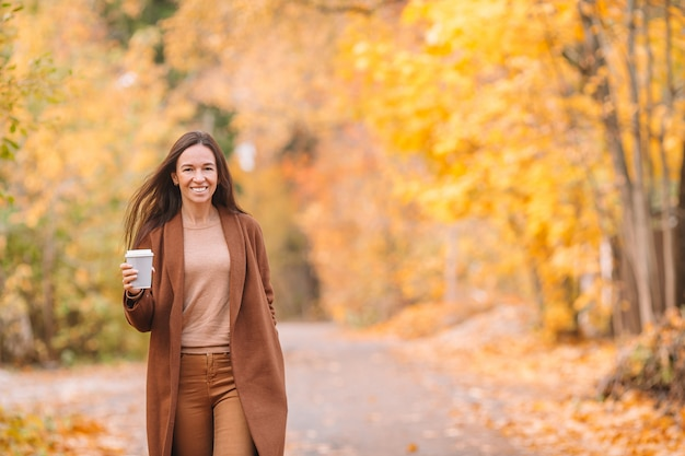 Fall concept - beautiful woman drinking coffee in autumn park under fall foliage Premium Photo