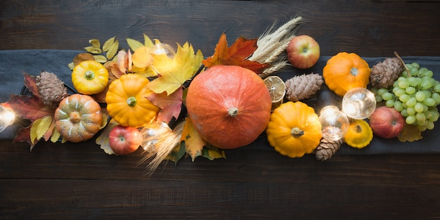 Fall decor for thanksgiving day with pumpkins, leaves, apples, lights on wooden table Premium Photo