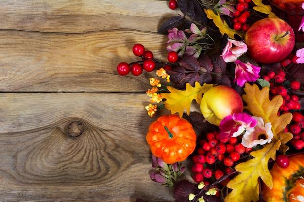 黄色のカシの葉、赤い果実、ピンクの花、コピースペースで秋の装飾 Premium写真