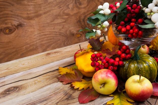 ナナカマドの果実、緑のカボチャ、オークの葉とリンゴのエンターピースの秋、コピースペース Premium写真