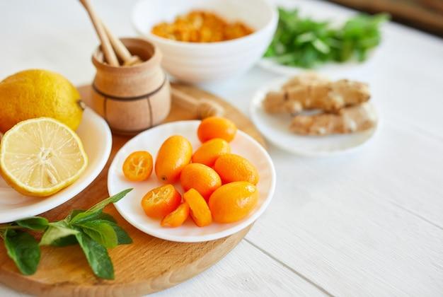 Fall immune system booste vitamin health. top view of fresh kumquat, sea buckthorn, ginger, lemon, honey, citrus and mint Premium Photo