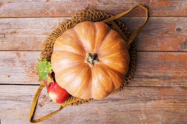 Падение тыквы в сетчатую хлопковую эко-сумку с яблоками, грибами кардончелли, грецкими орехами, листьями на старых деревянных досках. осенние покупки, урожай, ноль отходов Premium Фотографии