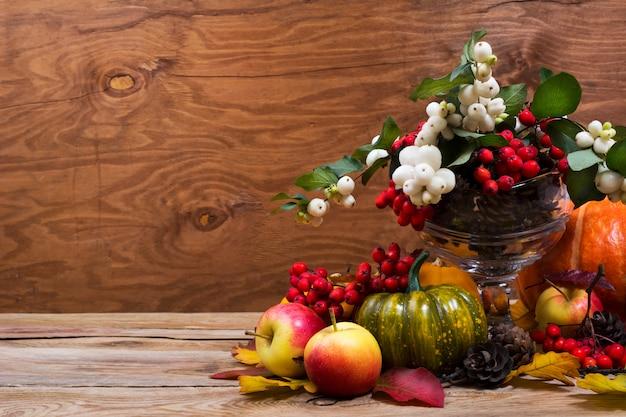 スノーベリー、緑のカボチャ、コピースペースのある秋のテーブルのセンターピース Premium写真