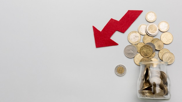 Fallen economy and jar with coins Premium Photo
