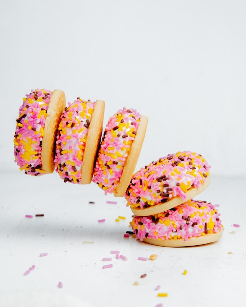 Falling bizet cakes with colorful glaze side view Free Photo