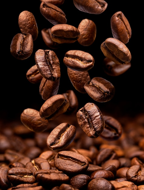 Falling coffee beans. dark with copy space Premium Photo
