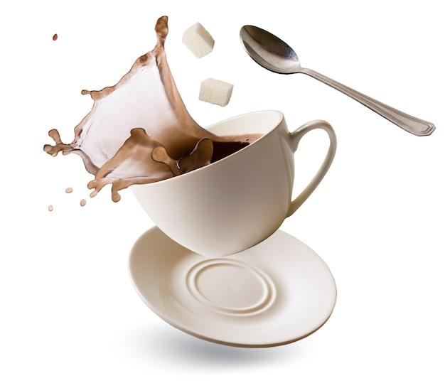 コーヒースプラッシュ、白砂糖のキューブと小さじ1杯と落下カップ Premium写真