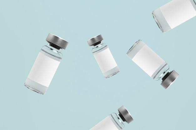 Bottiglie di vetro della fiala di iniezione che cadono con etichette bianche Foto Gratuite