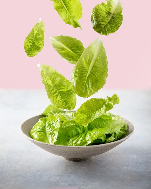 Falling lettuce leaves on pink background Premium Photo