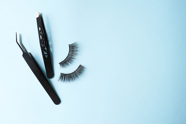 False eye lashes, black tweezers on blue background with copy space. Premium Photo