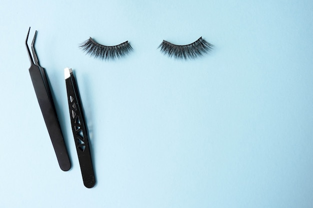 False eye lashes, black tweezers on blue background with copyspace Premium Photo