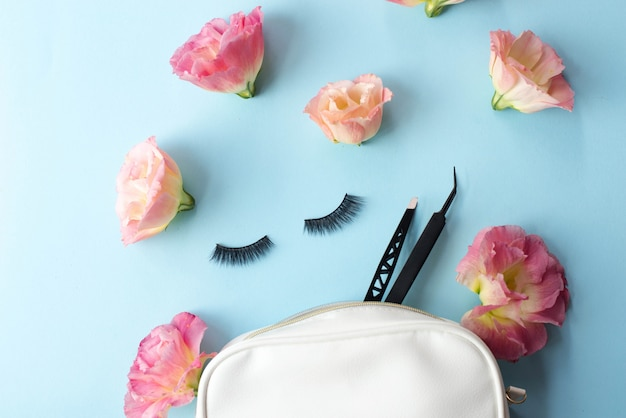 False eye lashes, black tweezers and pink flowers on blue. Premium Photo