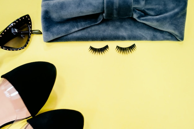 False eyelashes on color background, flat lay Premium Photo