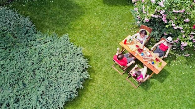 家族や夏のガーデンパーティーで屋外で一緒に食べる友達。上から食べ物や飲み物をテーブルの空撮。レジャー、休日、ピクニックのコンセプト Premium写真