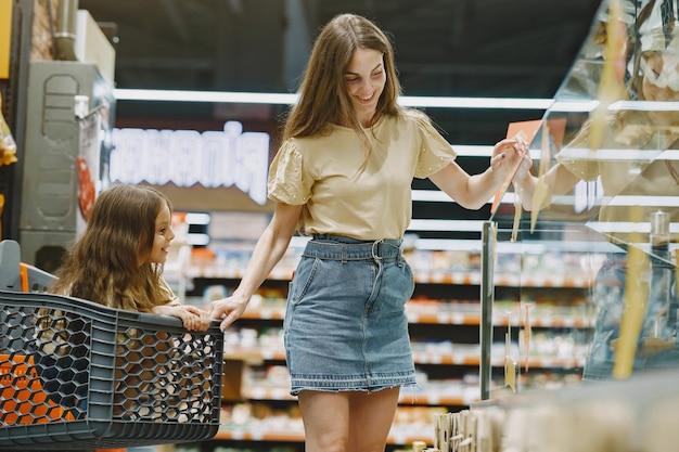 슈퍼마켓에서 가족. 갈색 T- 셔츠에있는 여자. 사람들은 제품을 선택합니다. 딸과 어머니. 무료 사진