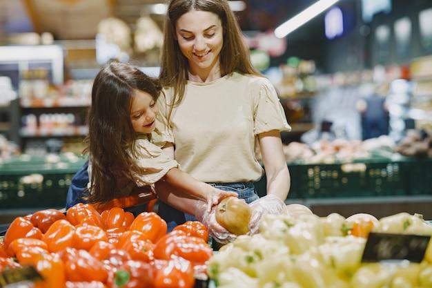 슈퍼마켓에서 가족. 갈색 T- 셔츠에있는 여자. 사람들은 야채를 선택합니다. 딸과 어머니. 무료 사진