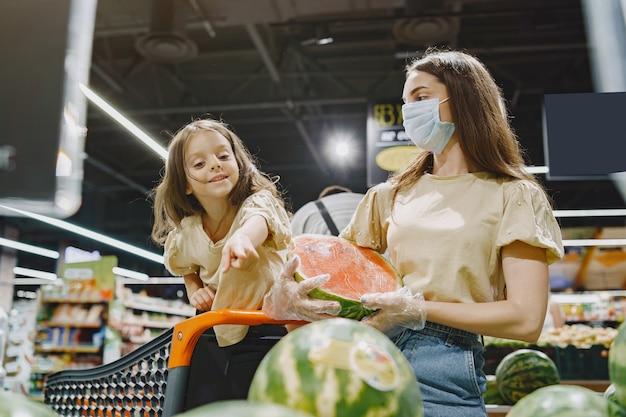 슈퍼마켓에서 가족. 보호 마스크에 여자입니다. 사람들은 야채를 선택합니다. 딸과 어머니. 코로나 바이러스. 무료 사진