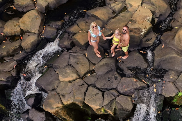 Family on the background of the rochester waterfall on the island of mauritius from a height.waterfall in the jungle of the tropical island of mauritius Premium Photo