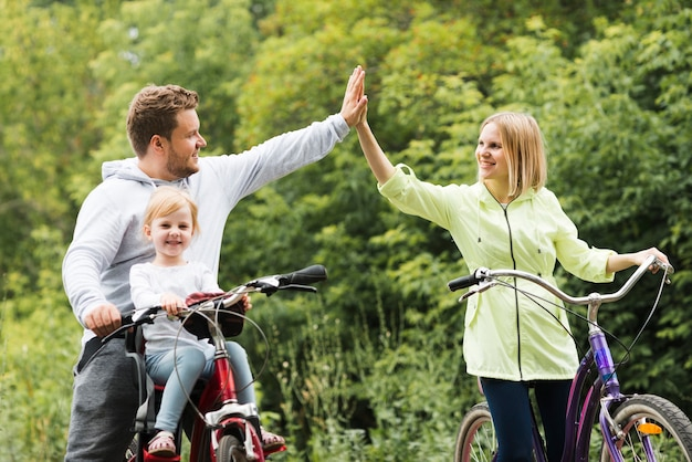 Family on bicycles giving high five Free Photo